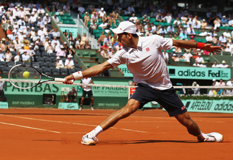 PARIS, FRANCE - MAY 28:  Novak Djokovic of Serbia plays a backhand in his men's singles first round match against Potito Starace of Italy during day 2 of the French Open at Roland Garros on May 28, 2012 in Paris, France.  (Photo by Matthew Stockman/Getty