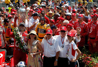 INDIANAPOLIS, IN - MAY 27:  Dario Franchitti of Scotland, driver of the #50 Target Chip Ganassi Racing Honda celebrates in victory lane with his wife actress Ashley Judd, team owner Chip Ganassi (2nd R) and his crew after he won the IZOD IndyCar Series 96
