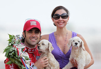 INDIANAPOLIS, IN - MAY 28:  Three time winner, Dario Franchitti of Scotland, driver of the #50 Target Chip Ganassi Racing Honda, poses with wife Ashley Judd and their dogs, on the yard of bricks during the  Indianapolis 500 Mile Race Trophy Presentation a