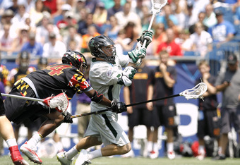 FOXBORO, MA - MAY 28:  Eric Lusby #12 of the Loyola Greyhounds scores as he lets go a shot while falling to the ground after be hit by Goran Murray #44 of the Maryland Terripans during the first half of the 2012 NCAA Division I Men's Lacrosse Championship