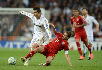 MADRID, SPAIN - APRIL 25:  Philipp Lahm of Bayern Munich tackles Cristiano Ronaldo of Real Madrid during the UEFA Champions League Semi Final second leg between Real Madrid CF and Bayern Munich at The Bernabeu Stadium on April 25, 2012 in Madrid, Spain.