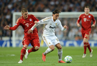 MADRID, SPAIN - APRIL 25:  Bastian Schweinsteiger of Bayern Munich battles for the ball with Mesut Ozil of Real Madrid during the UEFA Champions League Semi Final second leg between Real Madrid CF and Bayern Munich at The Bernabeu Stadium on April 25, 201