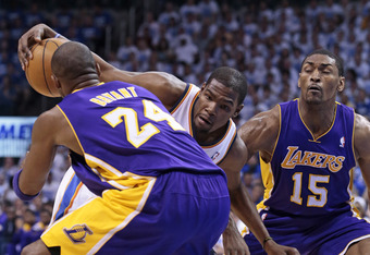 OKLAHOMA CITY, OK - MAY 16:   Kevin Durant #35 of the Oklahoma City Thunder tries to drive between Kobe Bryant #24 and Metta World Peace #15 of the Los Angeles Lakers in Game Two of the Western Conference Semifinals during the 2012 NBA Playoffs on May 16,