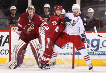 GLENDALE, AZ - APRIL 03:  Adrian Aucoin #33 of the Phoenix Coyotes attempts to clear Rick Nash #61 of the Columbus Blue Jackets away from goaltender Mike Smith #41 during the NHL game at Jobing.com Arena on April 3, 2012 in Glendale, Arizona.  (Photo by C