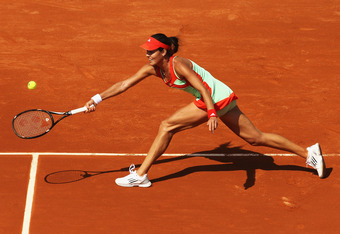 PARIS, FRANCE - MAY 27:  Ana Ivanovic of Serbia stretches to play a forehand during the women's singles first round match between Ana Ivanovic of Serbia and Lara Arrubarrena-Vecino of Spain on day one of the French Open at Roland Garros on May 27, 2012 in