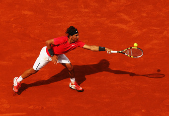 PARIS, FRANCE - MAY 31:  Rafael Nadal of Spain stretches for a backhand during his men's singles second round match against Denis Istomin of Uzbekistan during day five of the French Open at Roland Garros on May 31, 2012 in Paris, France.  (Photo by Clive