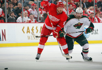 DETROIT, MI - MARCH 2:  Cal Clutterbuck #22 of the Minnesota Wild and Johan Franzen #93 of the etroit Red Wings battle for position during a NHL game at Joe Louis Arena on March 2, 2012 in Detroit, Michigan.  (Photo by Dave Sandford/Getty Images)