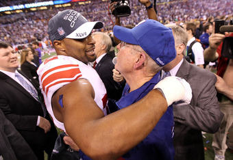 INDIANAPOLIS, IN - FEBRUARY 05:  Head coach Tom Coughlin of the New York Giants hugs Osi Umenyiora #72 on the field after defeating the New England Patriots in Super Bowl XLVI at Lucas Oil Stadium on February 5, 2012 in Indianapolis, Indiana. The New York