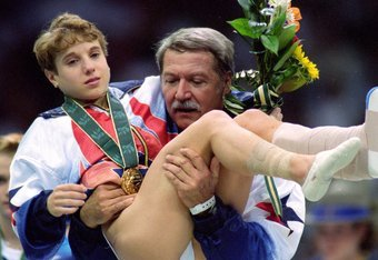 Kerri Strug is carried by her coach after completing the heroic vault in the 1996 Olympic Games.