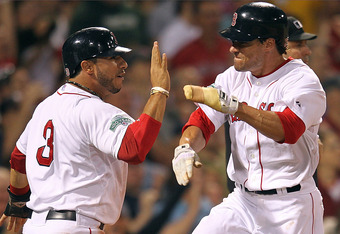 BOSTON, MA - MAY 29: Scott Podsednik #26 reacts with teammate Mike Aviles #3 of the Boston Red Sox after Podsednik scored when Daniel Nava #66 hit a three-run double against the Detroit Tigers in the fourth inning at Fenway Park May 29, 2012  in Boston, M