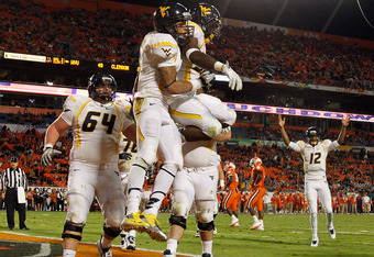 MIAMI GARDENS, FL - JANUARY 04:  Stedman Bailey (C) #3 and Ryan Clarke #32 (R of Bailey) of the West Virginia Mountaineers jump in the air as they celebrate after Bailey caught a 6-yard touchdown reception in the third quarter against the Clemson Tigers d