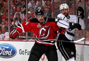 NEWARK, NJ - JUNE 02:  Adam Henrique #14 of the New Jersey Devils checks Willie Mitchell #33 of the Los Angeles Kings during Game Two of the 2012 NHL Stanley Cup Final at the Prudential Center on June 2, 2012 in Newark, New Jersey.  (Photo by Bruce Bennet