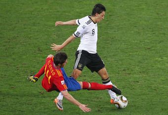 DURBAN, SOUTH AFRICA - JULY 07:  Xabi Alonso of Spain and Mesut Oezil of Germany battle for the ball during the 2010 FIFA World Cup South Africa Semi Final match between Germany and Spain at Durban Stadium on July 7, 2010 in Durban, South Africa.  (Photo