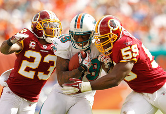 MIAMI GARDENS, FL - NOVEMBER 13:  Brandon Marshall #19 of the Miami Dolphins catches a pass guarded by  DeAngelo Hall #23 and  London Fletcher #59 of the Washington Redskins during a game  at Sun Life Stadium on November 13, 2011 in Miami Gardens, Florida