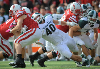 LINCOLN, NE - OCTOBER 29: Linebacker Max Bullough #40 of the Michigan State Spartans reaches for running back Rex Burkhead #22 of the Nebraska Cornhuskers during their game at Memorial Stadium October 29, 2011 in Lincoln, Nebraska.  Nebraska defeated Mich