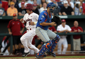 OMAHA, NE - JUNE 28:  Peter Mooney #6 of the South Carolina Gamecocks scores a run in front of Mike Zunino #3 of the Florida Gators during game 2 of the men's 2011 NCAA College Baseball World Series at TD Ameritrade Park Omaha on June 28, 2011 in Omaha, N