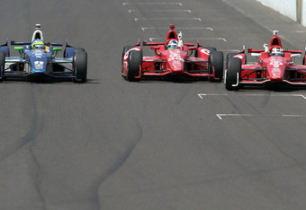 INDIANAPOLIS, IN - MAY 27:  Dario Franchitti (C) of Scotland, driver of the #50 Target Chip Ganassi Racing Honda crosses the yard of bricks start/finish line to take the checkered flag ahead of teammate Scott Dixon (R) of New Zealand, driver of the #9 Tar