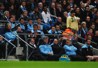 MANCHESTER, ENGLAND - MARCH 21:  Carlos Tevez of Manchester City (back row 2nd left) sits on the bench alongside team mates during the Barclays Premier League match between Manchester City and Chelsea at the Etihad Stadium on March 21, 2012 in Manchester,