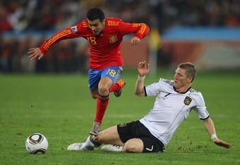DURBAN, SOUTH AFRICA - JULY 07: Pedro (l) of Spain jumps a challenge from Bastian Schweinsteiger of Germany during the 2010 FIFA World Cup South Africa Semi Final match between Germany and Spain at Durban Stadium on July 7, 2010 in Durban, South Africa.
