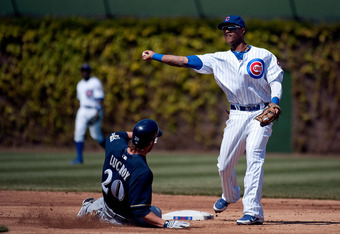 CHICAGO, IL - APRIL 12:   Shortstop Starlin Castro #13 of the Chicago Cubs (R) throws to first base to complete a double play on a ground ball hit by Cesar Izturis #3 of the Milwaukee Brewers as Jonathan Lucroy #20 slides into second base during the secon