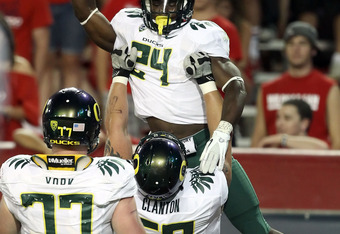 TUCSON, AZ - SEPTEMBER 24:  Runningback Kenjon Barner #24 of the Oregon Ducks is hoisted up by Ryan Clanton #60 after scoring on a 6 yard rushing touchdown against the Arizona Wildcats during the second quarter of the college football game at Arizona Stad