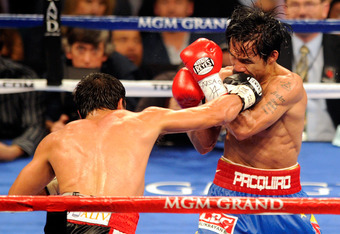 LAS VEGAS, NV - NOVEMBER 12:  Juan Manuel Marquez (L) throws a right at Manny Pacquiao during the ninth round of their WBO world welterweight title fight at the MGM Grand Garden Arena November 12, 2011 in Las Vegas, Nevada. Pacquiao retained his title wit