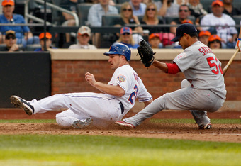 NEW YORK, NY - JUNE 02:  Daniel Murphy #28 of the New York Mets slides in ahead of the tag of Eduardo Sanchez #52 of the St. Louis Cardinals and scores on a past ball at Citi Field on June 2, 2012 in the Flushing neighborhood of the Queens borough of New