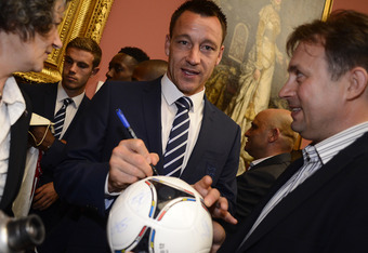 KRAKOW, POLAND - JUNE 07:  John Terry (C) signs a football during a civic reception as the England squad attend a team gala welcome reception at the Polish Art Museum ahead of EURO 2012 on June 7, 2012 in Krakow, Poland. (Photo by Nigel Roddis - Pool / Ge