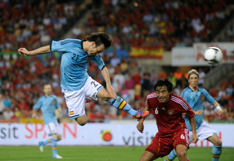 SEVILLE, SPAIN - JUNE 03:  David Silva (L) of Spain heads the ball beside Feng Xiaoting of China during the International Friendly match between Spain and China at La Cartuja stadium on June 3, 2012 in Seville, Spain.  (Photo by Denis Doyle/Getty Images)
