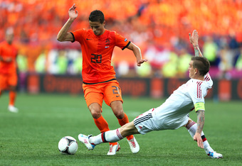 KHARKOV, UKRAINE - JUNE 09:  Daniel Agger of Denmark tackles Ibrahim Afellay of Netherlands during the UEFA EURO 2012 group B match between Netherlands and Denmark at Metalist Stadium on June 9, 2012 in Kharkov, Ukraine.  (Photo by Ian Walton/Getty Images