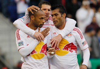 HARRISON, NJ - MARCH 31:  Thierry Henry #14 of the New York Red Bulls celebrates his frist half goal with teammate Wilman Conde #2 and Kenny Cooper #33 against the Montreal Impact at Red Bull Arena on March 31, 2012 in Harrison, New Jersey. The Red Bulls