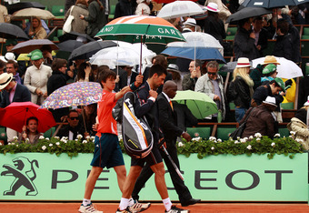 PARIS, FRANCE - JUNE 10:  Novak Djokovic of Serbia walks off the court after rain interrupted play during the men's singles final against Rafael Nadal of Spain on day 15 of the French Open at Roland Garros on June 10, 2012 in Paris, France.  (Photo by Cli