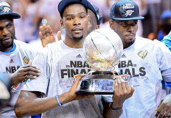 OKLAHOMA CITY, OK - JUNE 06:  Kevin Durant #35 of the Oklahoma City Thunder celebrates with the trophy as Serge Ibaka #9 looks on after defeating the San Antonio Spurs to win the Western Conference Finals of the 2012 NBA Playoffs at Chesapeake Energy Aren