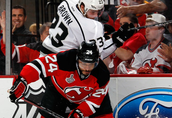 NEWARK, NJ - JUNE 09:  Dustin Brown #23 of the Los Angeles Kings checks Bryce Salvador #24 of the New Jersey Devils during Game Five of the 2012 NHL Stanley Cup Final at the Prudential Center on June 9, 2012 in Newark, New Jersey.  (Photo by Bruce Bennett