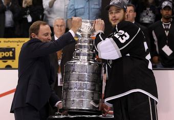 LOS ANGELES, CA - JUNE 11:  Captain Dustin Brown #23 of the Los Angeles Kings receives the Stanley Cup from NHL Commissioner Gary Bettman after the Kings defeated the New Jersey Devils 6-1 to win the Stanley Cup in Game Six of the 2012 Stanley Cup Final a