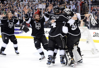 LOS ANGELES, CA - JUNE 11:  (L-R) Captain Dustin Brown #23, Jarret Stoll #28, Colin Fraser #24, Drew Doughty #8 of the Los Angeles Kings surround goaltender Jonathan Quick #32 of the Los Angeles Kings after winning Game Six of the 2012 Stanley Cup Final 6