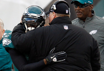 PHILADELPHIA, PA - JANUARY 01:  Michael Vick #7 of the Philadelphia Eagles hugs head coach Andy Reid after Vick threw a touchdown pass against the Washington Redskins during the second half at Lincoln Financial Field on January 1, 2012 in Philadelphia, Pe