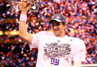 INDIANAPOLIS, IN - FEBRUARY 05:  Super Bowl MVP Eli Manning #10 of the New York Giants celebrates with the Vince Lombardi Trophy after the Giants won 21-17 against the New England Patriots during Super Bowl XLVI at Lucas Oil Stadium on February 5, 2012 in