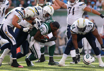 EAST RUTHERFORD, NJ - OCTOBER 23:  Shonn Greene #23 of the New York Jets has his helmet pulled off by Corey Liuget #94 of the San Diego Chargers at MetLife Stadium on October 23, 2011 in East Rutherford, New Jersey.  (Photo by Nick Laham/Getty Images)