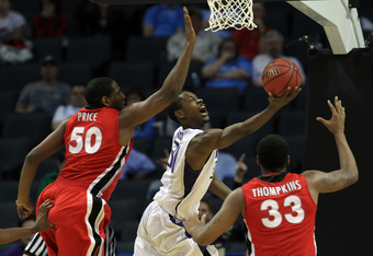 CHARLOTTE, NC - MARCH 18:  Terrence Ross #31 of the Washington Huskies goes up for a shot between Jeremy Price #50 and Trey Thompkins #33 of the Georgia Bulldogs in the second half during the second round of the 2011 NCAA men's basketball tournament at Ti