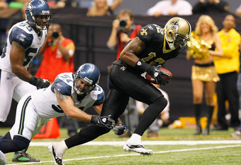 NEW ORLEANS - NOVEMBER 21:  Marques Colston #12 of the New Orleans Saints scores a touchdown as he breaks a tackle by Lofa Tatupu #51 of the Seattle Seahawks at Louisiana Superdome on November 21, 2010 in New Orleans, Louisiana.  (Photo by Kevin C. Cox/Ge
