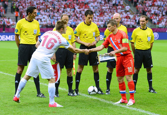 WARSAW, POLAND - JUNE 12: Jakub Blaszczykowski of Poland  shakes hands with Andrey Arshavin of Russia ahead of the UEFA EURO 2012 group A match between Poland and Russia at The National Stadium on June 12, 2012 in Warsaw, Poland.  (Photo by Shaun Botteril