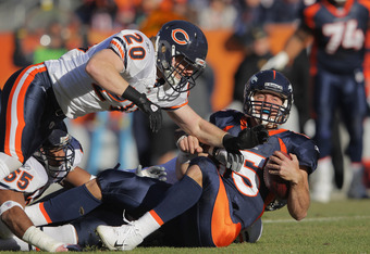 DENVER, CO - DECEMBER 11:  Tim Tebow #15 of the Denver Broncos is sacked by Israel Idonije #71 of the Chicago Bears (hidden) with help from Craig Steltz #20 at Sports Authority Field at Mile High on December 11, 2011 in Denver, Colorado.  (Photo by Doug P