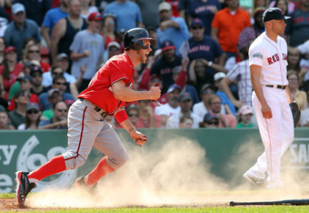 BOSTON, MA - JUNE 10:  Bryce Harper #34 of the Washington Nationals scores the go-ahead run in the ninth inning as pitcher Alfredo Aceves #91 of the Boston Red Sox looks away during interleague play at Fenway Park June 10, 2012  in Boston, Massachusetts.