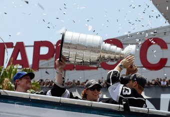 LOS ANGELES, CA - JUNE 14:  Los Angeles Kings team members from (L-R) Jonathan Quick #32, Matt Greene #2, Anze Kopitar #11 and Dustin Brown #23 hold the Stanley Cup to cheering fans during the Stanley Cup victory parade on June 14, 2012 in Los Angeles, Ca