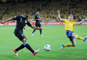 KIEV, UKRAINE - JUNE 15:  Theo Walcott of England crosses as Sebastian Larsson of Sweden tries to block it during the UEFA EURO 2012 group D match between Sweden and England at The Olympic Stadium on June 15, 2012 in Kiev, Ukraine.  (Photo by Christopher