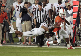 MIAMI, FL - OCTOBER 27: Chase Minnifield #13 of the Virginia Cavaliers attempts to tackle Travis Benjamin #3 of the Miami Hurricanes as he runs with the ball on October 27, 2011 at Sun Life Stadium in Miami, Florida. (Photo by Joel Auerbach/Getty Images)