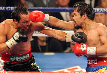 LAS VEGAS, NV - NOVEMBER 12:  Manny Pacquiao (R) throws a right at Juan Manuel Marquez during the ninth round of their WBO world welterweight title fight at the MGM Grand Garden Arena November 12, 2011 in Las Vegas, Nevada. Pacquiao retained his title wit