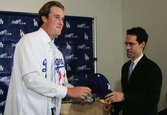 LOS ANGELES - JANUARY 12:  Right handed pitcher Derek Lowe (L) receives a hat from General Manager Paul DePodesta during a press conference after signing a four-year contract with the Los Angeles Dodgers January 12, 2005 at Dodger Stadium in Los Angeles,