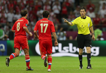 WARSAW, POLAND - JUNE 12: Referee Wolfgang Stark has words with Konstantin Zyryanov and Alan Dzagoev of Russia during the UEFA EURO 2012 group A match between Poland and Russia at The National Stadium on June 12, 2012 in Warsaw, Poland.  (Photo by Alex Gr